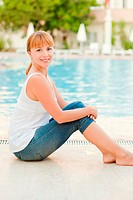 Smiling woman in jeans nearby pool