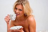 naked blonde with tea in her bedroom