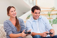Smiling couple playing video games in their living room