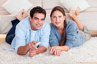 Lovely couple watching TV while lying on a carpet in their living room