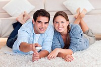 Smiling couple watching TV while lying on a carpet in their living room