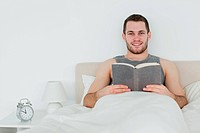 Man reading a book in his bedroom