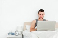 Man using a laptop in his bedroom