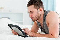 Handsome man using a tablet computer while lying on his belly in his bedroom