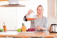 Woman pouring self made fruit juice into a glass