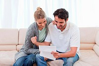 Cheerful couple reading a letter in their living room