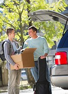 Father helping teenage son 16_17 packing to college