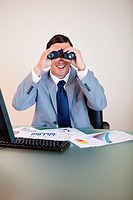Smiling businessman at his desk looking through binoculars