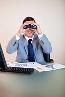 Smiling businessman at his desk looking through binoculars