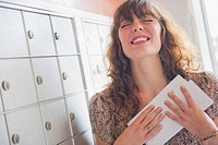 Happy woman holding letters near mail box