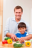 Father and son cutting vegetables together