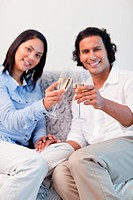 Young couple celebrating with sparkling wine in the living room