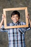 Portrait of smiling boy 8_9 looking through frame, studio shot