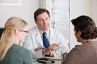 Male doctor talking to patients in his office