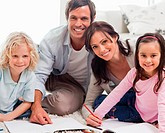 Smiling family drawing together in a living room