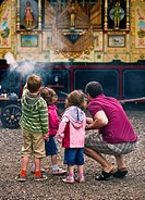 England, Essex, Audley End. Father and children looking at a steam organ at the Audley End Steam Gala 2011.