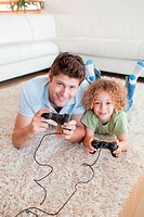 Portrait of a boy and his father playing video games while lying on a carpet