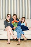 Portrait of grandmother and grand daughters 8_9, 14_15 sitting on sofa