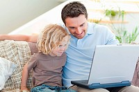 Father and son together with laptop on the sofa
