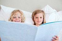 Brother and sister reading bedtime story together