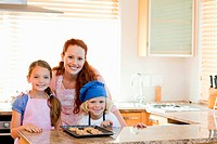 Mother together with children and cookies in the kitchen