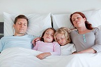 Young family sleeping in the bed together