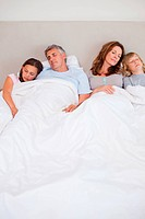 Family sleeping in the bedroom together