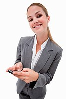 Portrait of a smiling businesswoman using a smartphone against a white background