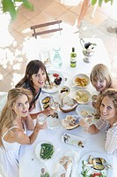 Women eating at table outdoors
