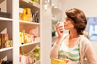 Woman smelling candles in store