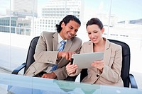 Happy business team using a tablet computer in an office