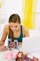Teenage girl doing her homework and using her computer, while eating sweets, cookies, and drinking energy drinks