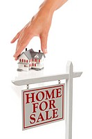 Womans Hand Choosing Home with Real Estate Sign in Front