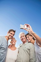Parents and adult children taking self_portrait with digital camera