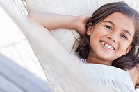 Portrait of smiling girl laying on hammock with hands behind head