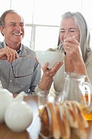 Senior couple laughing at breakfast (thumbnail)