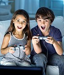 Brother and sister playing video games in living room (thumbnail)