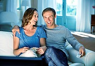 Happy couple watching TV on sofa (thumbnail)