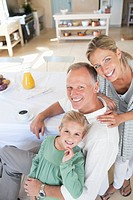 Portrait of smiling parents with daughter at breakfast table (thumbnail)