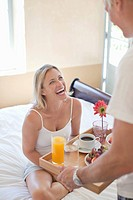 Man bringing breakfast on tray to smiling woman in bed