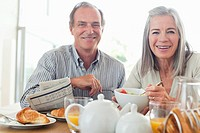 Portrait of smiling senior couple eating breakfast at table