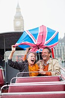 Rain falling on couple with British Flag umbrella on double decker bus