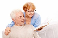 The elderly couple reads the book on a white background