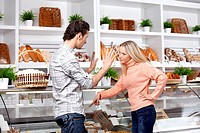 The young couple quarrels in a baker´s shop