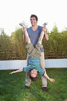 Father holding son upside_down in grass