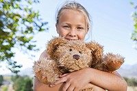 Close up portrait of smiling girl hugging teddy bear