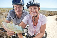 Portrait of smiling senior couple on bicycles holding map on beach path