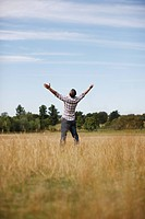 Man with arms outstretched in rural field