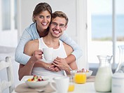 Portrait of smiling couple enjoying breakfast at table