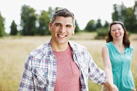 Portrait of smiling couple holding hands in rural field (thumbnail)